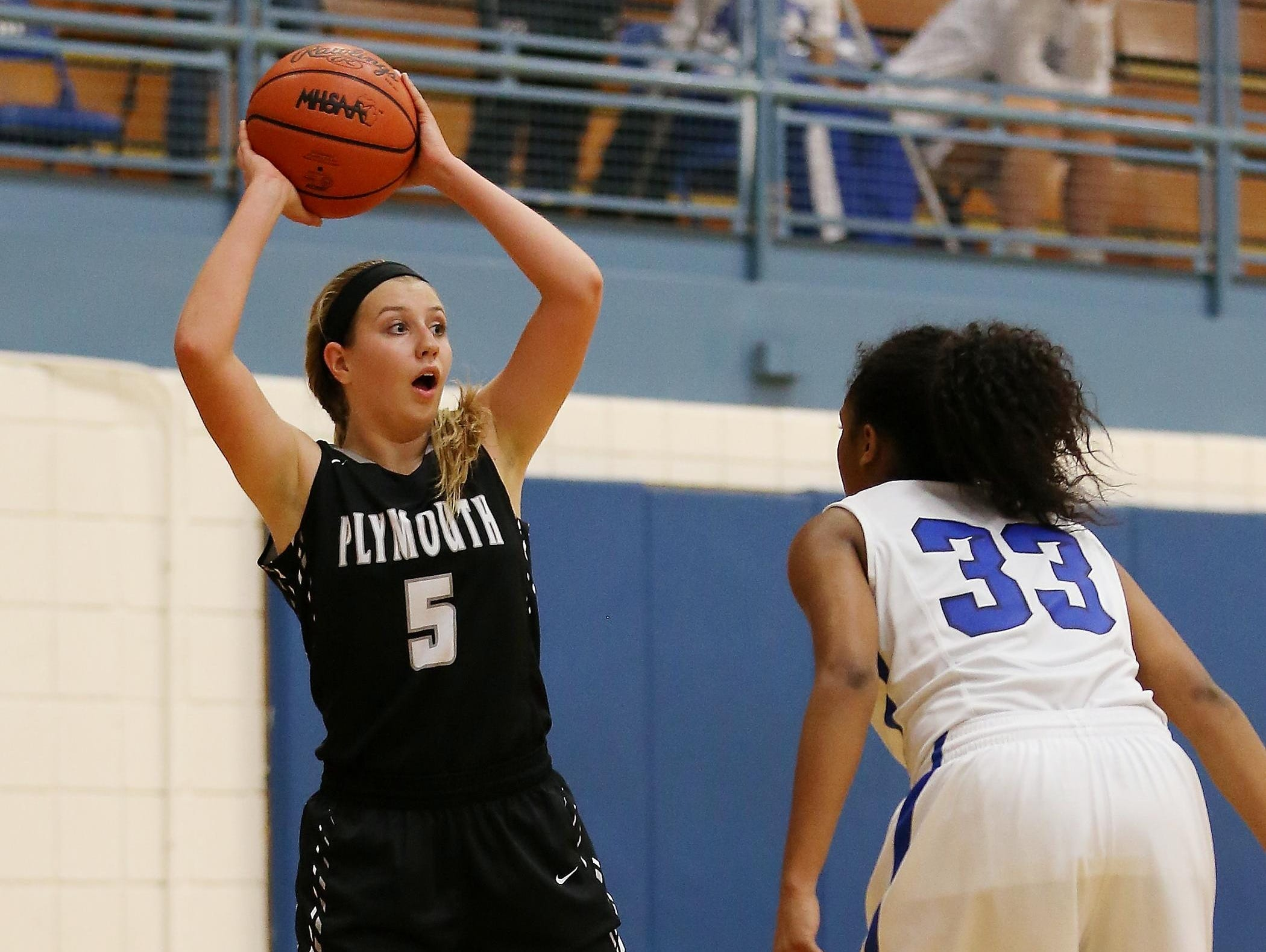 Plymouth's Hannah Badger looks for a teammate to pass the ball to, while Salem's Zoe Talley guards her.