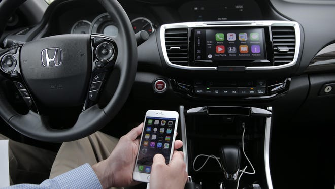 Chris Martin of Honda North America demonstrates Apple CarPlay in Torrance, Calif. Playing deejay with voice commands will get easier for more Americans as some cars get updated with software that integrates smartphones into the dashboard.