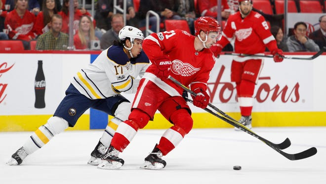 Sabres center Jordan Nolan (17) tries to get the puck from Red Wings center Dylan Larkin (71) during the first period on Friday, Nov. 17, 2017, at Little Caesars Arena.