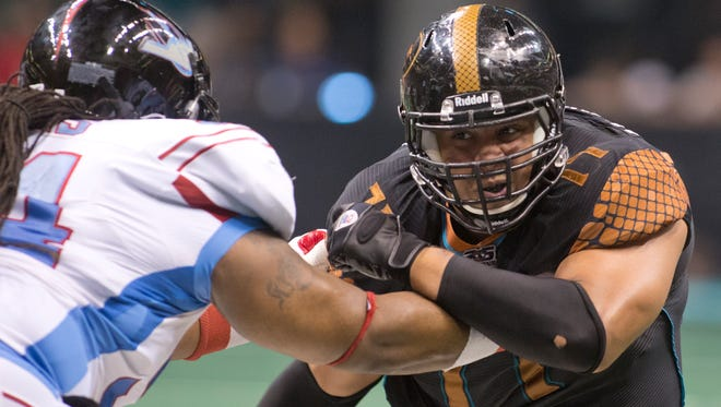 Arizona Rattlers' Anttaj Hawthorne fights to get to the Kansas City Command quarterback at the US Airways Center in Phoenix on July 21, 2012.