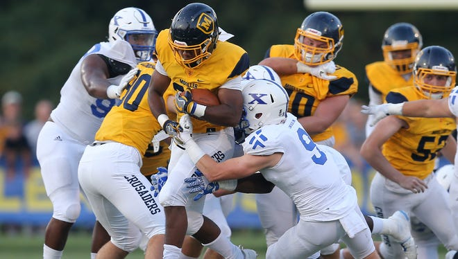 Moeller running back Christian Neidhard Jr. (28) carries the ball in the first quarter during the high school football game between the St. Xavier Bombers and Moeller Crusaders, Friday, Sept. 22, 2017, at Roettger Stadium in Lockland, Ohio.