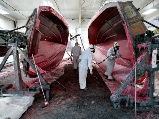 Workers apply fiberglass to the resin frame of a boat