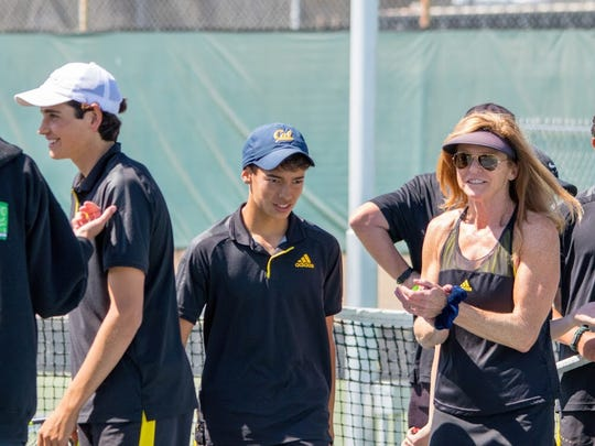Ventura High boys tennis coach Tracie Johnstone Currie, left, and her players celebrate after winning a Division 3 first-round match Wednesday.