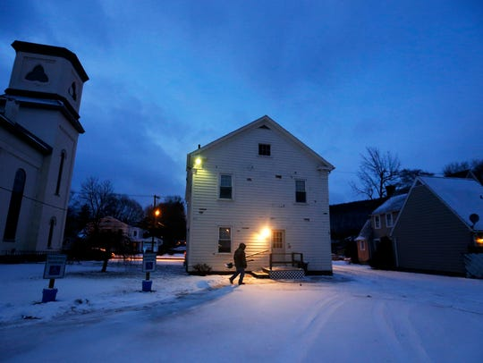 An AIMS Maintenance worker shovels the property of