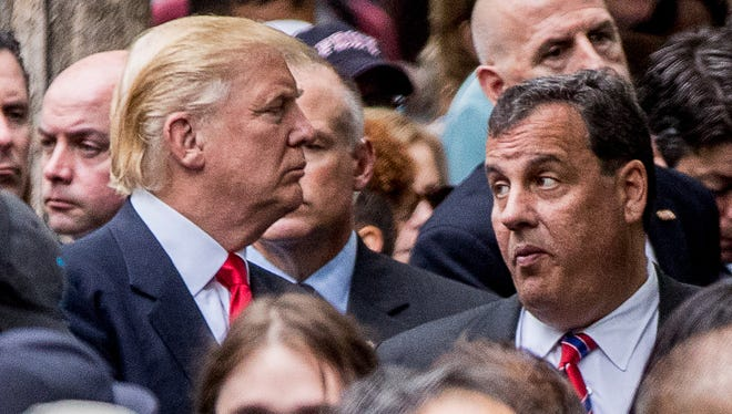 Republican presidential candidate Donald Trump, left, speaks with New Jersey Gov. Chris Christie, right, as he attends a ceremony at the Sept. 11 memorial, in New York.