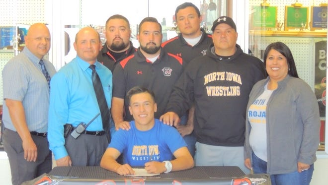 Robert Rodriguez signed a letter of intent to wrestle for North Iowa Community College. The Indian sits while his supporters are from left, Cobre athletic director Pat Abalos, principal Frank Quarrel, coach Johnny Gallegos, coach Jared Gallegos, coach Laramie Perrault, father Robert Rodriguez II and mother Tina Rodriguez.