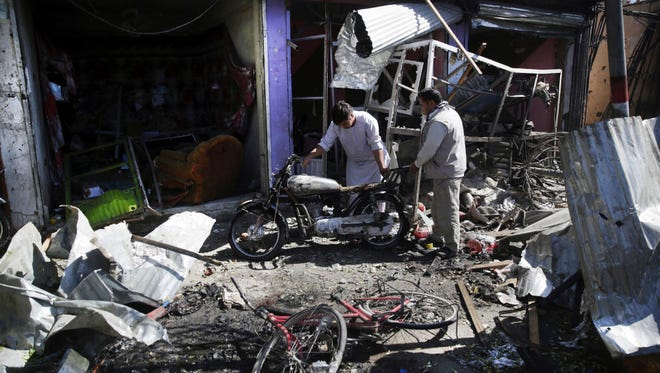 Men look at the remains of their properties at the site of a suicide attack in Kabul, Afghanistan, on July 24.