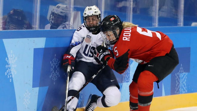 United States forward Kendall Coyne (26) passes the puck as she is hit by Canada defenseman Lauriane Rougeau (5) during the second period.