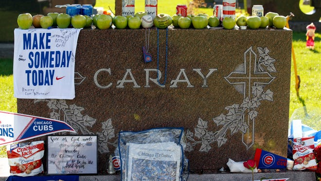 Numerous items are displayed at the grave of the late Chicago Cubs broadcaster Harry Caray, the day after the Cubs won the World Series.
