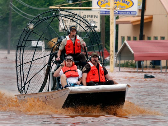Highway patrolmen rescue Justin Nimmo, left, from his business, Just-In-Time, after flooding caused by rising water from Saturday night's storms trapped him in the store on Sunday in Purcell, Okla.