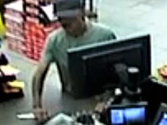 A man puts a knife on the counter during robbery at