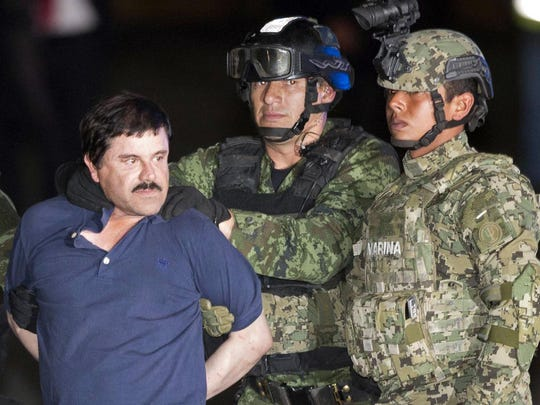 """Joaquin """"El Chapo"""" Guzman is made to face the press as he is escorted to a helicopter in handcuffs by Mexican soldiers and marines at a federal hangar in Mexico City, Mexico, following his recapture six months after escaping from a maximum security prison."""