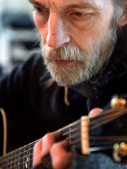 Jimmy Abegg plays his guitar in his studio Tuesday,