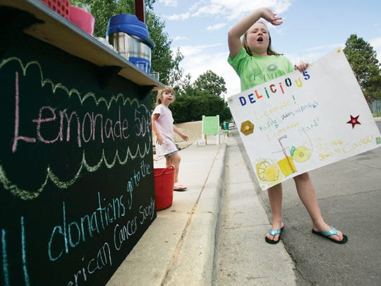 At right, Keely Stockham, 10, attempts to flag down drivers to try her lemonade in July 2011.