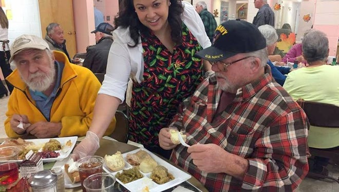 1st New Mexico Bank employee Yevette Tarazon laid down plates for senior citizens on Tuesday at the annual Deming Senior Citizen's Center Thanksgiving Dinner on Tuesday.