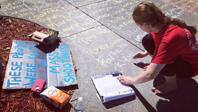 Sarah Brown, 17, wrote nearly 600 names in chalk at Fort Myers High School Saturday of those killed in mass shootings since 2000.