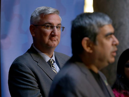 Governor Eric Holcomb,left, listens to the announcement
