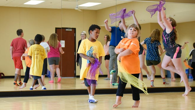 Children exercise using scarves and expressive dance Wednesday, July 12, at the YMCA.