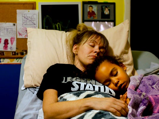 Amy Bailey and her daughter Sydney cuddle in the early morning hours before Amy heads to physical therapy and Sydney goes to school. Dec. 12, 2016