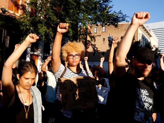 "Demonstrators raise their fists during a moment of silence for Sam DuBose on Vine Street in Over-the-Rhine during ""Rally and Street Action: Demand a Retrial"" Justice for Sam DuBose sponsored by Black Lives Matter: Cincinnati Saturday, July 8, 2017. The rally was in protest of the second mistrial of Ray Tensing. Tensing, a former University of Cincinnati police officer was charged with murder and voluntary manslaughter in the shooting death of Sam DuBose during a traffic stop in July 2015."