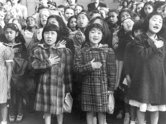 In this April 1942 file photo made available by the Library of Congress, children at the Weill public school in San Francisco recite the Pledge of Allegiance. Some of them are evacuees of Japanese ancestry who will be housed in War Relocation Authority centers for the duration of World War II. Throughout American history, during times of war and unrest, authorities have cited various reasons and laws to take children away from their parents. Examples include Native American boarding schools, Japanese internment camps and deportations that happened during the Great Depression.