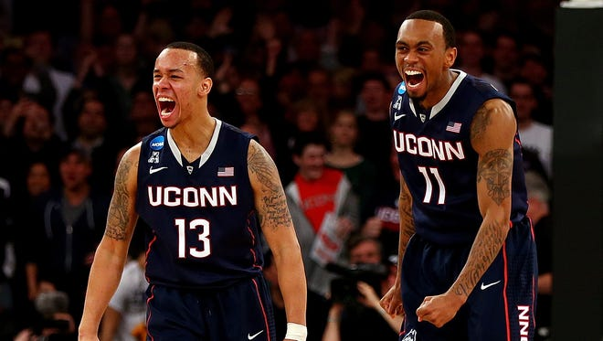 Shabazz Napier and Ryan Boatright of the Connecticut Huskies react after a play late in the game against the Michigan State Spartans.