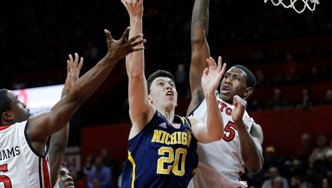 Michigan forward Sean Lonergan (20) takes a shot as he splits Rutgers defenders guard Mike Williams (5) and forward Greg Lewis (35) during the first half of an NCAA college basketball game Tuesday, Jan. 20, 2015, in Piscataway, N.J.