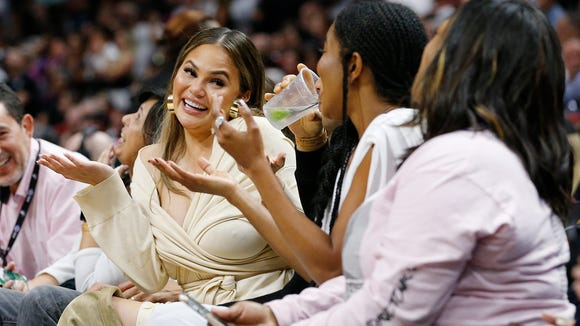 Chrissy Teigen reacts after Dwyane Wade crashed into her causing her to spill her drink on her husband, John Legend.