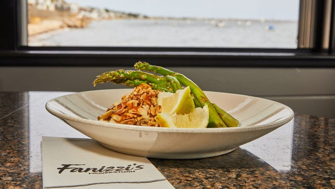 Mustard Nut Crusted Cod, one of the most popular dishes at Fanizzi's Restaurant By the Sea, is photographed with a view of Cape Cod Bay. Part of the restaurant's dining area sits on pilings and offers a 180-degree view of the bay.