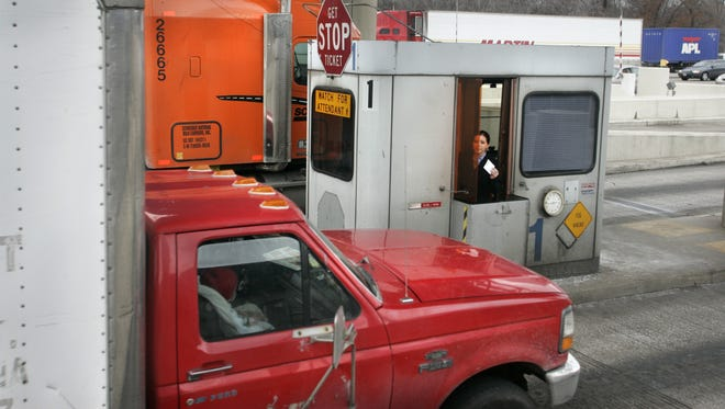 Indiana Toll Road worker Elyse Soto (cq), prepares to hand a trucker a toll ticket for an eastbound trip along Interstate 80/90 on Tuesday, Jan. 24, 2006.
