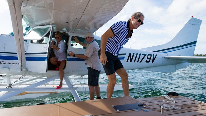 Caroleigh, left, and Scott Trettenero, right, of Fort Myers, exit a seaplane with the help of Jon Rector, center, director of operations for Salt Island Seaplanes, after flying to Key West from Naples on Friday, Nov. 6, 2015. The business offers flights  in a Cessna seaplane from Naples Municipal Airport to water landings off Key West.
