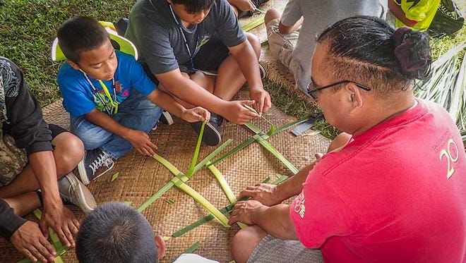 Pa'a Taotao Tano member instructs youths in pandanus weaving.