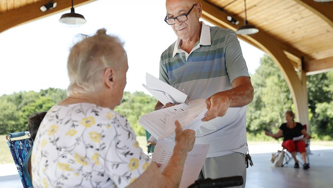 Jim DiRocco hands music to Bernice Filaccio, of Weymouth. They are members of the Whippoorwill singers who usually entertain at the Weymouth Senior Center and local nursing homes. The singers are practicing informally while social distancing at the King Oak Hill Park.