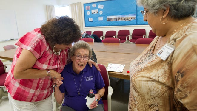 Kathy Jones, left, and Anita Olguin congratulate Shirley Glandon, center, on 50 years of volunteer service at the Abilene State Supported Living Center on June 30, 2015.