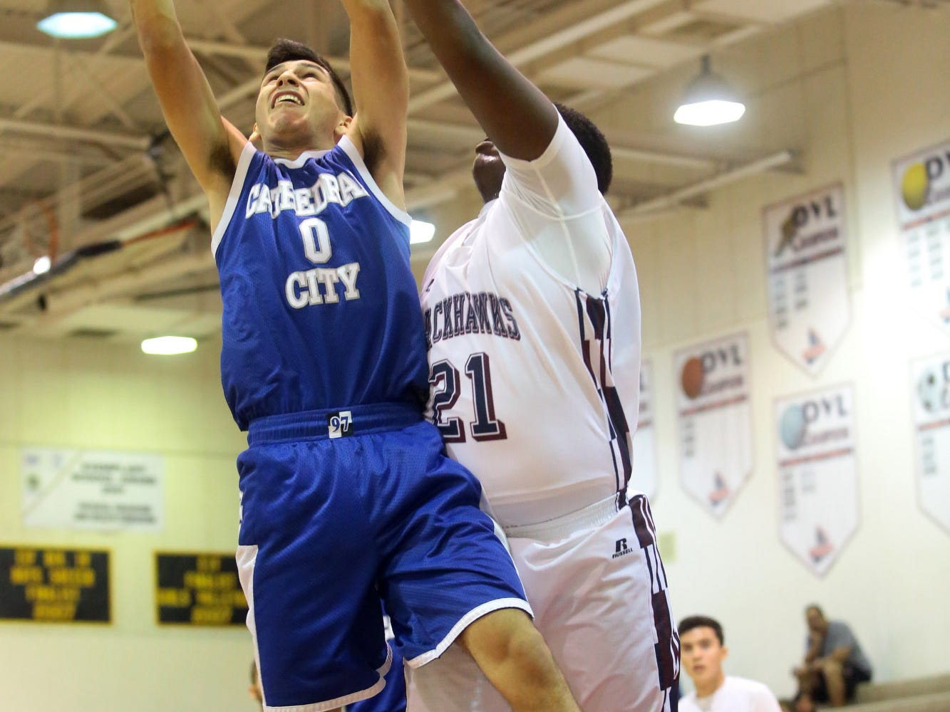 Nick Jimenez of Cathedral City (0, blue) beats La Quinta's Charles Hays (21, white) to pull down a defensive rebound on Tuesday night. La Quinta won, 74-59, and stays atop the league.