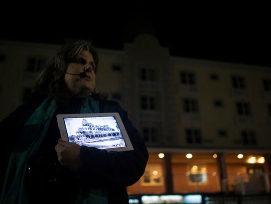 Chesapeake Ghost Walks guide Mindie Burgoyne shows a photo of the Plinhimmon Hotel, now the Plim Plaza after the hotel burned down in the 1960s, during a tour in Ocean City.