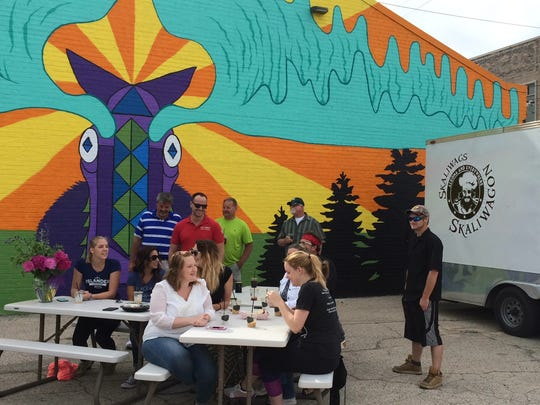 Au Naturale Cosmetics employees hang out near Morty the Moose ahead of Thursday's kickoff of Lunch with Morty. Every Thursday, food trucks will congregate at the east side mural for lunch.