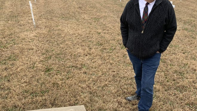 John Burchill, a professor of criminal justice at Kansas Wesleyan University, looks at the wood crosses inside the Saline County Cemetery where the Poor Farm used to be dating back to 1871.