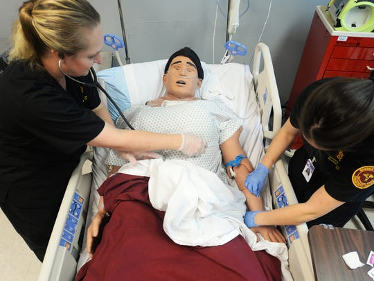 Barbara Thompson, left, and Tabitha Schwartz work on a dummy patient in the BPCC nursing lab.