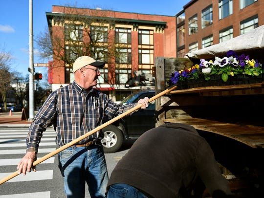 Steve Barkdoll of Why Not Greenhousees in Dover Township uses a pole to retrieve flats of pansies from his truck in York's Continental Square.