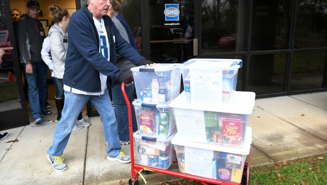 United Way volunteer Jim Jackson help load boxes of food for Thanksgiving to be delivered to Williamson County families on Thursday, Nov. 16, 2017.