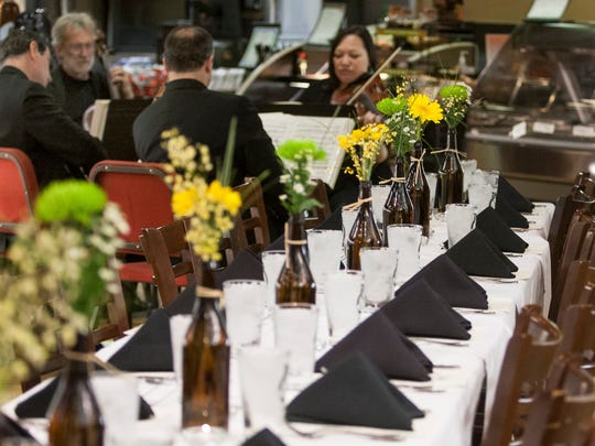 Two tables for 22, lined with flowers in beer bottles, in Janssen's Market April 3 for a pop-up dinner.