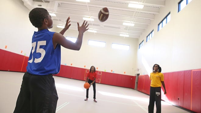 Students, from left, Darrell Bruce, sixth grade, Shawnique Hagen, seventh grade, and K'Lah Gause, fifth grade,  play ball inside the large new gym, part of the recent addition at PUC Achieve Charter School on Mark Street in Rochester last week.