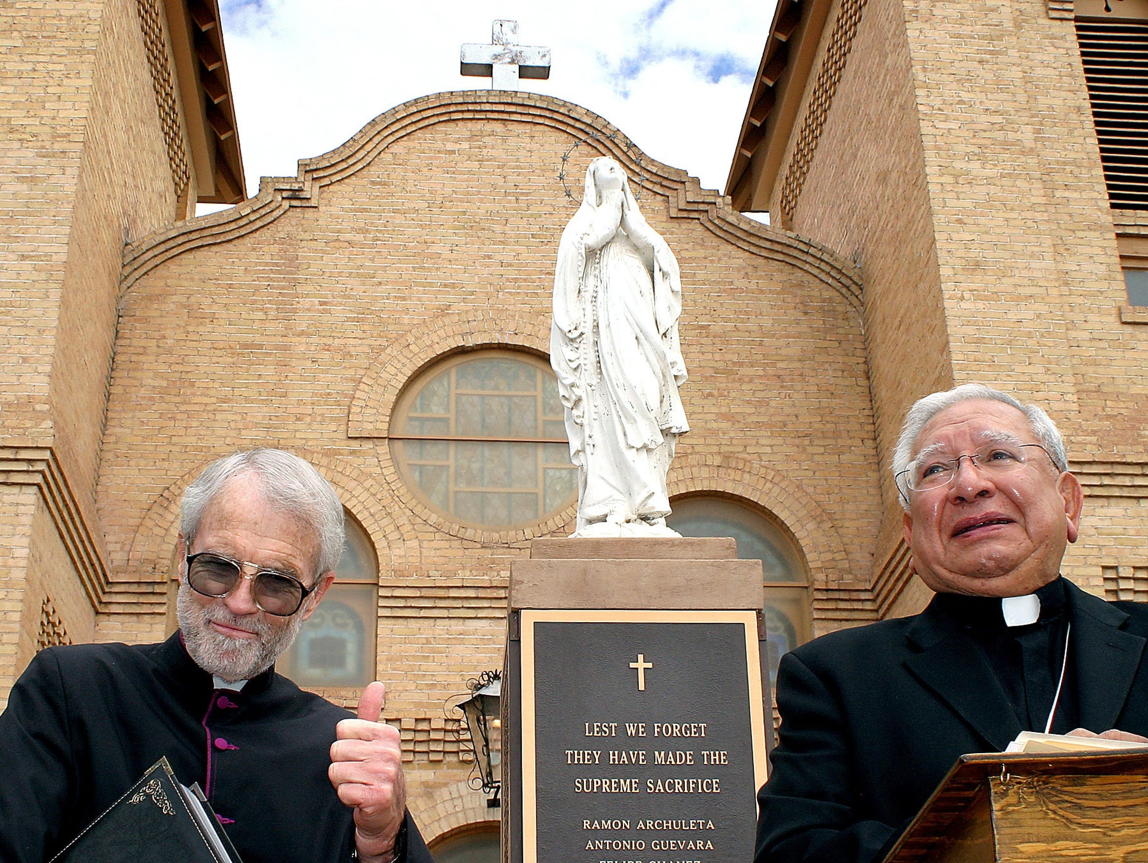 Monsignor Robert L. Getz, left, gives a thumbs-up as Bishop Ricardo Ramirez proudly announces that the Vatican has elevated the status of San Albino Church in Mesilla to that of basilica.