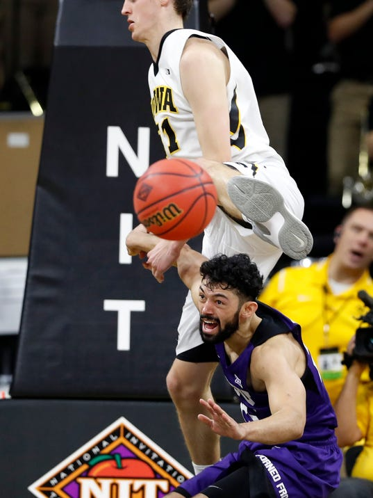 TCU guard Alex Robinson fights for a loose ball with Iowa forward Nicholas Baer, top, during the second half of a second-round game in the NIT college basketball tournament, Sunday, March 19, 2017, in Iowa City, Iowa. TCU won 94-92. (AP Photo/Charlie Neibergall)