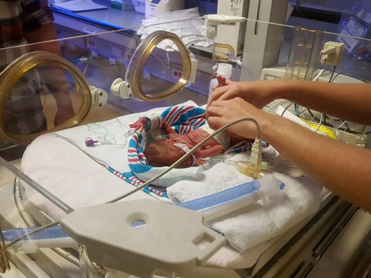 Piper Beejack is dwarfed by a set of hands shortly after her birth at Monmouth Medical Center.