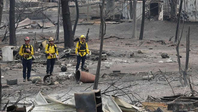 San Bernardino County Fire Department firefighters assess the damage to a neighborhood in the aftermath of a wildfire on July 29, 2018, in Keswick, Calif.