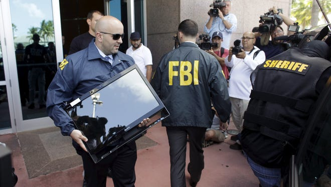 An FBI agent brings out a computer after an operation inside the CONCACAF (Confederation of North, Central America and Caribbean Association Football) offices in Miami Beach, Florida May 27, 2015. The world's most popular sport was plunged into turmoil on Wednesday as seven powerful soccer figures were arrested on U.S. corruption charges and faced extradition from Switzerland, whose authorities also announced a criminal investigation into the awarding of the next two World Cups. REUTERS/Javier Galeano
