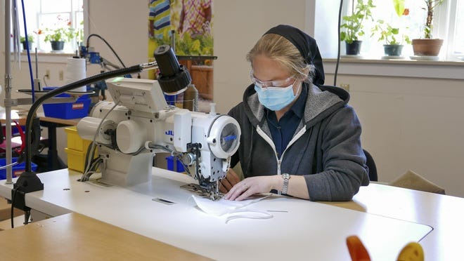 A member of the Bruderhof sews a PPE mask.