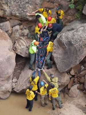 Search and rescue team members carry a body after it was found along Pine Creek, Wednesday, Sept. 16, 2015, in Zion National Park, near Springdale.